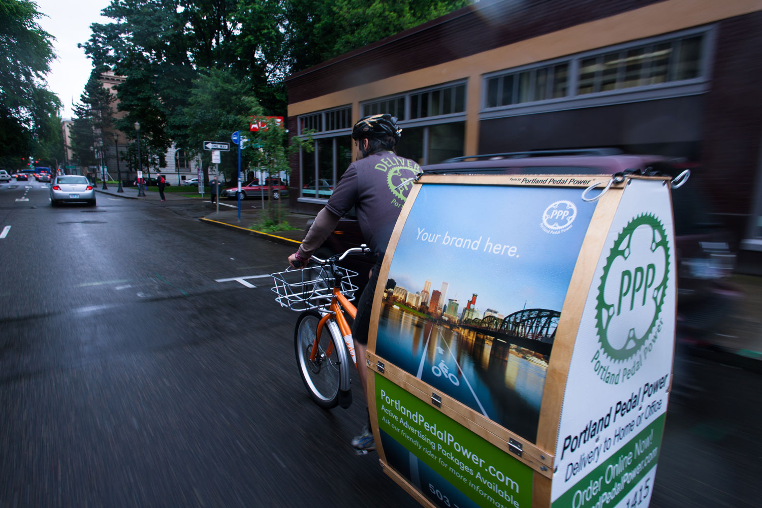 A Portland Pedal Power Rider biking through downtown Portland delivering and catering